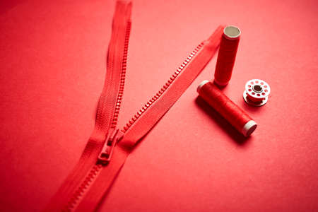 threads and zipper on a red minimalistic background Stock Photo