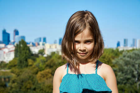 charming girl in a dress posing on a city skyline in summer Stock Photo