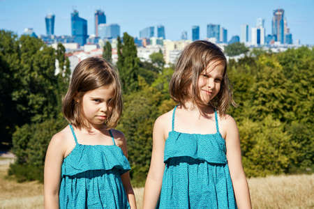 two cute girls in dresses are posing on the city skyline in summer Stock Photo