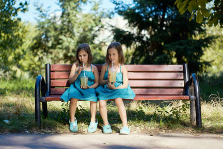 two cute little girls in dresses sit on a bench and drink lemonade in the summer