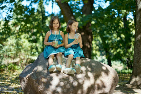 two cute little girls in dresses sit on a stone and drink lemonade