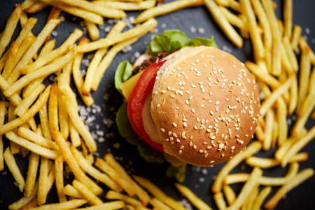 delicious cheeseburger surrounded by french fries on a black table