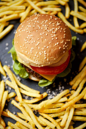 cheeseburger surrounded by french fries on a black table Banco de Imagens - 160161451