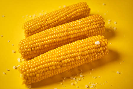 delicious boiled sweet corn on yellow background