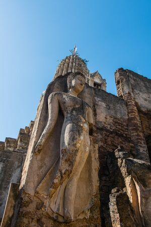 Ancient sandstone Buddha standing in front of the temple Stock Photo