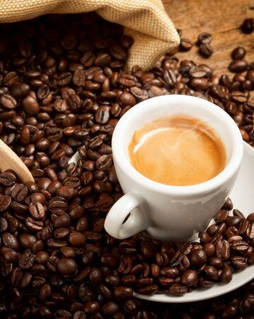 coffe bean: Taza de caf� espresso caliente con los granos de caf� en la mesa de madera