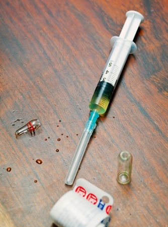 Syringe with medicine on wooden table photo