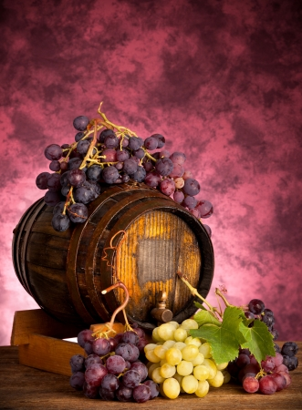 White and red grapes with wine barrel on wood table photo