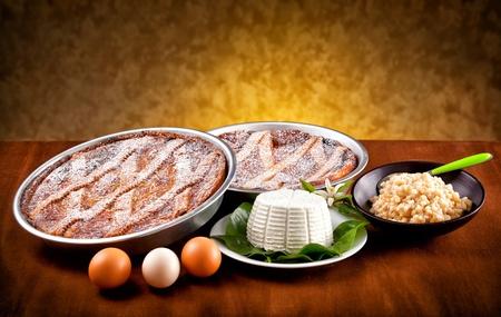napoletana: Pastiera napoletana con ingredienti sul tavolo di legno