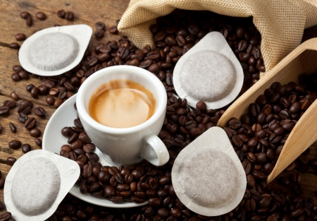 pods: Coffee cups with pods on rustic table Stock Photo