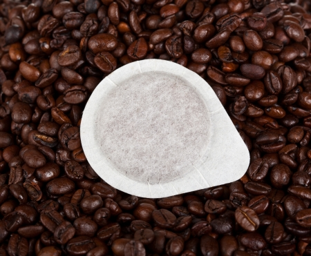 Coffee pods on coffee beans background photo