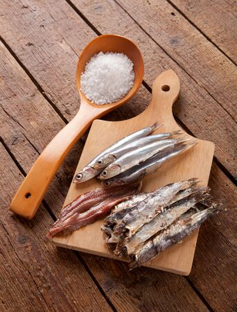 Marinated anchovies on wooden table photo