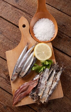 Marinated anchovies on wooden table Imagens
