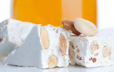 Sweet nougat with almonds on white background photo