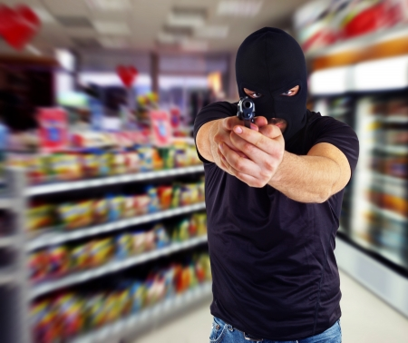 thievery: Man in a mask with a gun in the supermarket Stock Photo