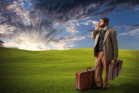 emigration: Emigrant man with the suitcases in the field
