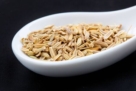 fennel seeds: Fennel seeds in the spoon on black background Stock Photo