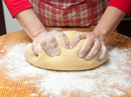 levadura: Manos femeninas en masa de harina en la mesa de amasar closeup