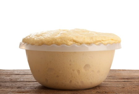 leavening: Rising Yeast Dough in bowl on wooden table Stock Photo