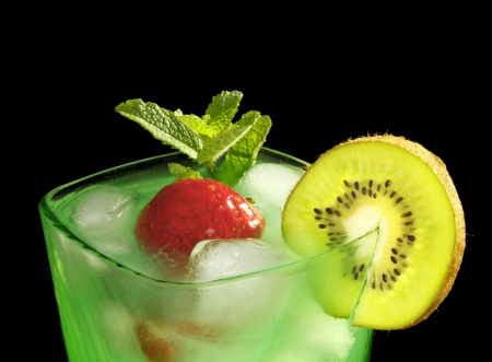 minted: Mint drink with strawberries and kiwi on black background Stock Photo