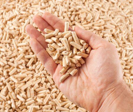 Wood pellets in hand on pellets background photo