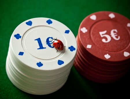 Ladybugs with poker chips on green table photo