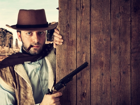 Bad gunman in the old wild west indicates with the gun a wooden plank