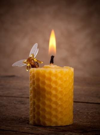 lighted: Lighted beeswax candles on wooden table