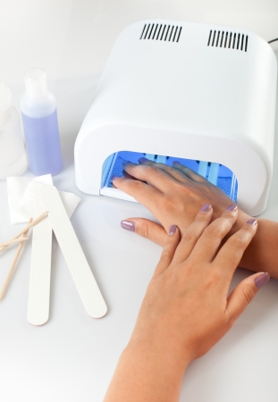 manicure salon: Hands with uv lamp for nails Stock Photo