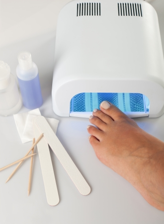 Feet with uv lamp for nails photo