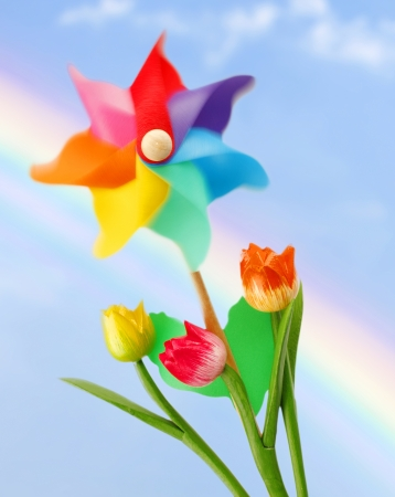 Colorful pinwheel on blue sky with rainbow photo