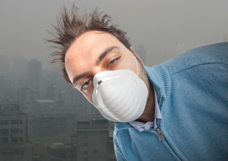 depletion: Young boy with mask respiratory protection near industrial city Stock Photo