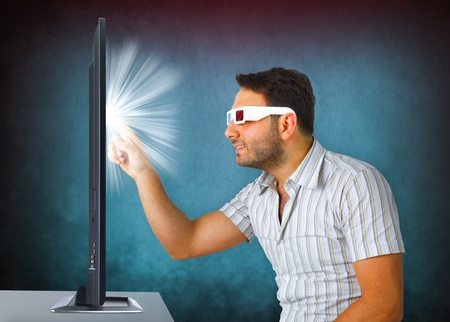 Portrait Of A Young Man Wearing 3d Glasses touches the tv photo