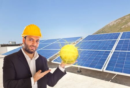 Businessman with big solar panel and yellow helmet photo