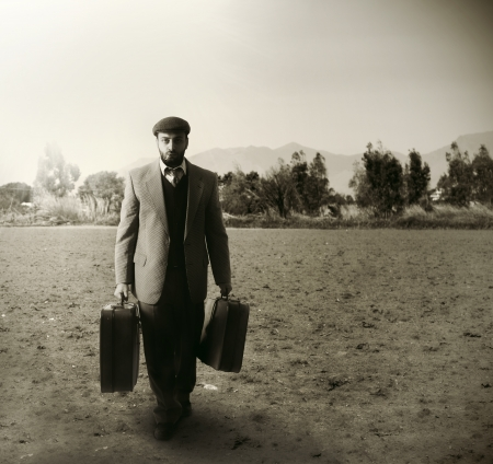 emigrant: Emigrant man with the suitcases in an agricultural field