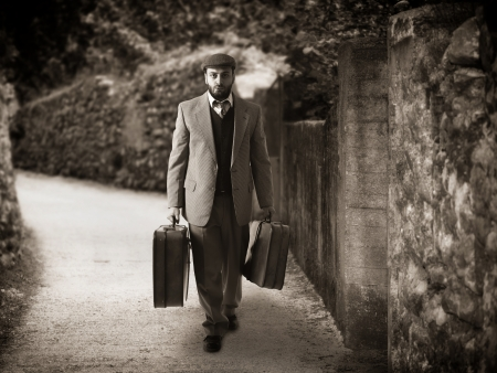 emigrant: Emigrant man with the suitcases in a narrow country