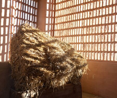Barn with the sun  from outside and straw and hay  photo