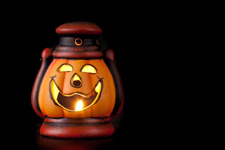 pumpkin lantern with candle inside lit up in the dark photo