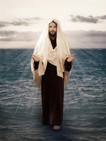 biblia: Jes�s camina sobre el agua con la luz detr�s de �l