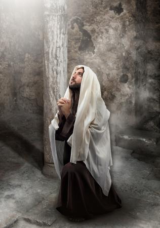 イエスは光に向かって祈りでひざまずきます。 写真素材