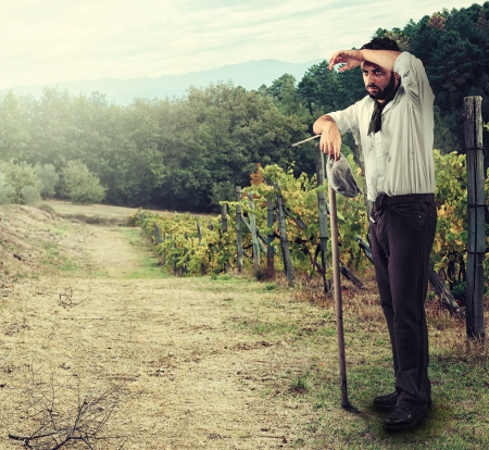 hoe: Tired Farmer in the vineyard leaning on the hoe Stock Photo