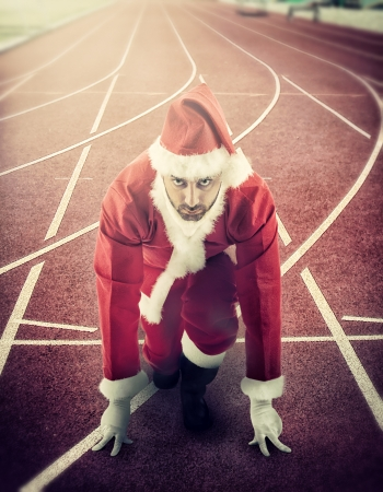 starting: Santa Claus in the starting position on a running track. Stock Photo