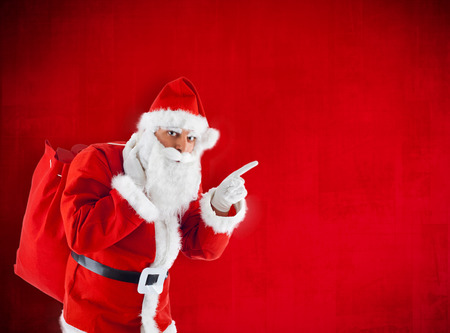 Santa Claus with sack pointing in blank red. photo