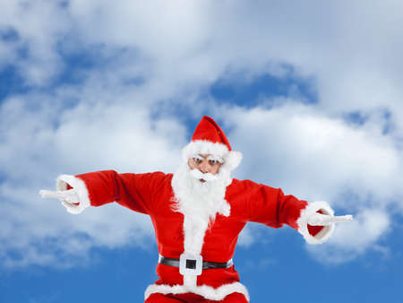 Santa Claus mimics a plane while flying in the sky photo
