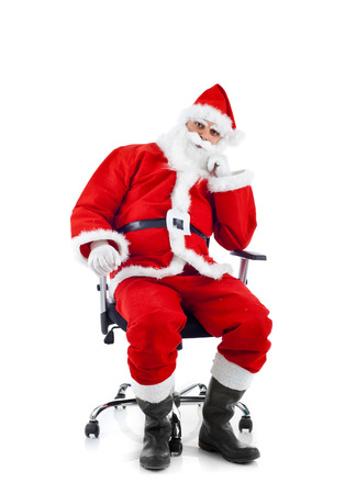 Young Santa Claus sitting on an office chair on white background. photo