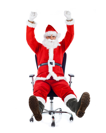 Young Santa Claus sitting on an office chair on white background. Stock Photo