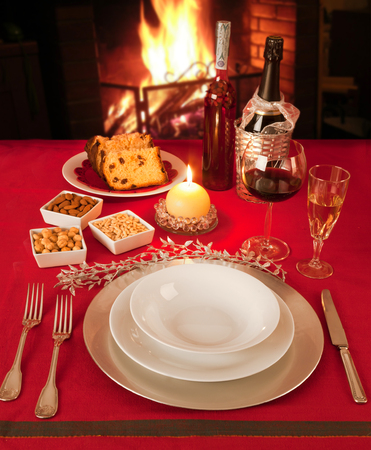 Christmas table near the fireplace, set for a single person. photo