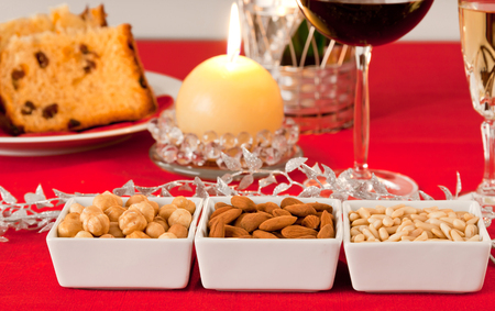 Pine nuts, almonds and hazelnuts in bowls on the Christmas table. photo