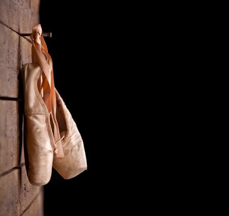 zapatillas de ballet: Viejos zapatos de ballet rosados ??usados ??colgando sobre fondo de madera