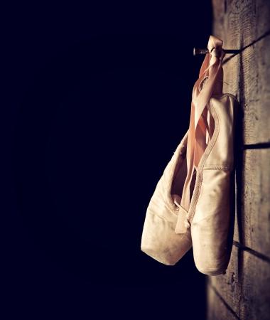 ballet cl�sico: Viejos zapatos de ballet rosados ??usados ??colgando sobre fondo de madera